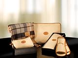 KIT DE BIENVENIDA (POLIPIEL) | Conjunto de manta 100% lana australiana, neceser y zapatillas en fundas de polipiel con chapón grabado, presentado en un elegante packaging: caja negra con tapa y bolsa de regalo blanca con personalización en stamping plata.