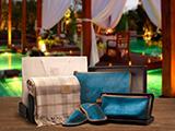 KIT DE BIENVENIDA (SERRAJE) | Conjunto de manta 100% lana australiana y zapatillas en fundas de serraje grabadas, presentado en un elegante packaging: caja negra con tapa y bolsa de regalo blanca con personalización en stamping plata.